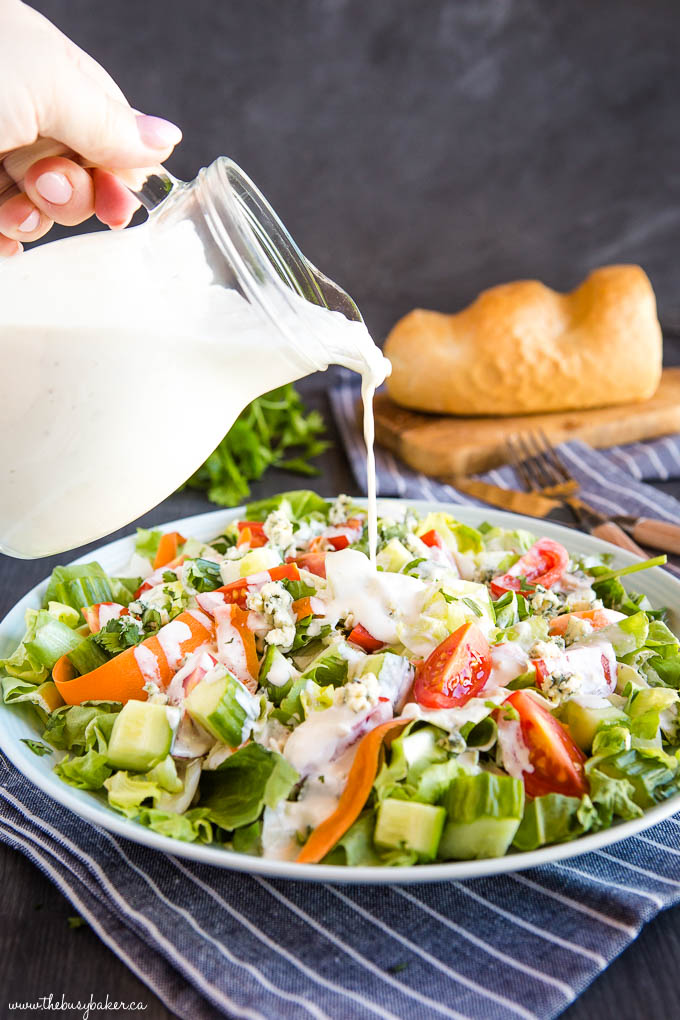 pouring keto blue cheese dressing on garden salad