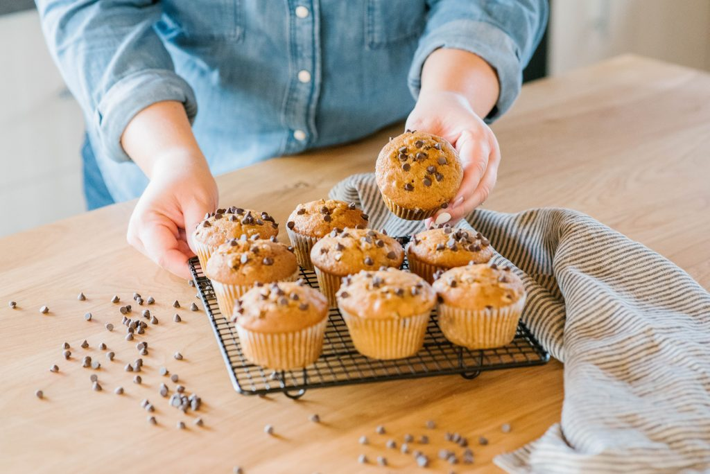 woman in kitchen with chocolate chip pumpkin muffins