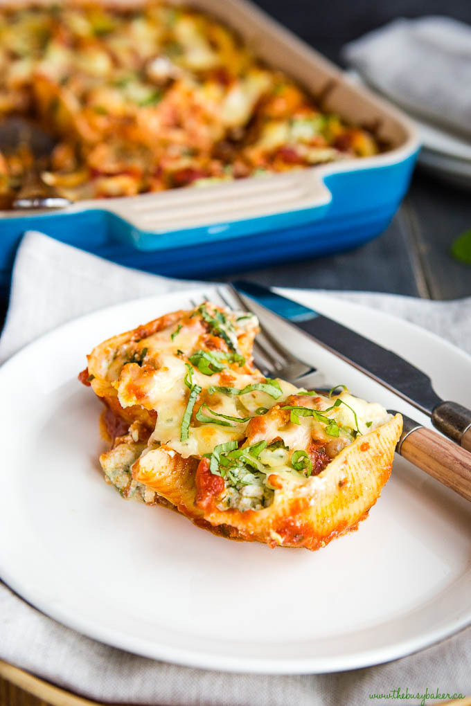 stuffed shells with ricotta on plate with fork and knife