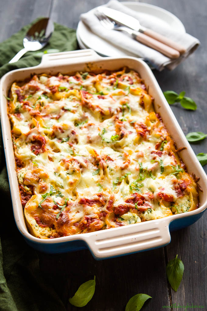 cheesy pasta dinner in casserole dish with fresh basil on top