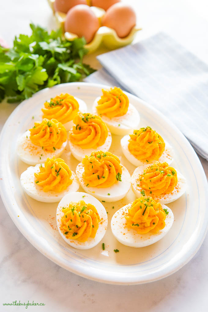 deviled eggs with chives on a platter