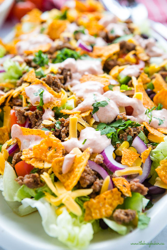 close up image of beef taco salad with lettuce, cheese, onion, beef and Doritos