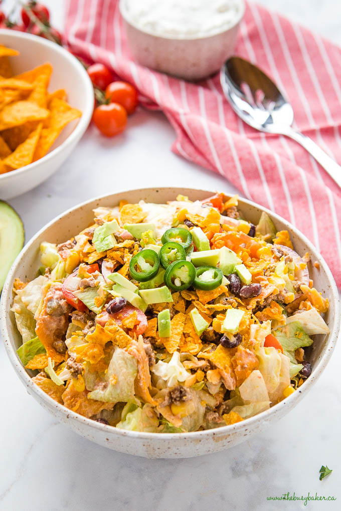 ground beef taco salad in bowl with crunchy tortilla chips and jalapenos on top
