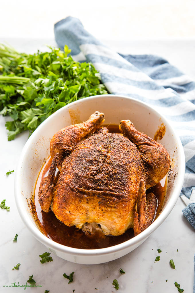 whole baked chicken with super crispy skin in white baking dish