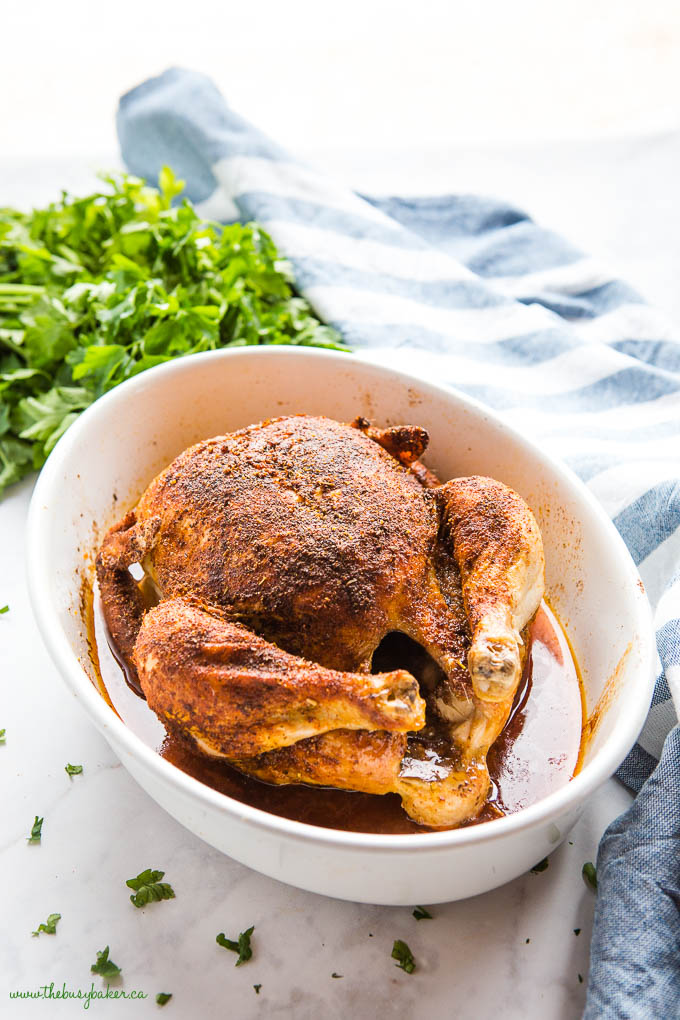 overhead photo shows whole chicken with crispy skin in white baking dish