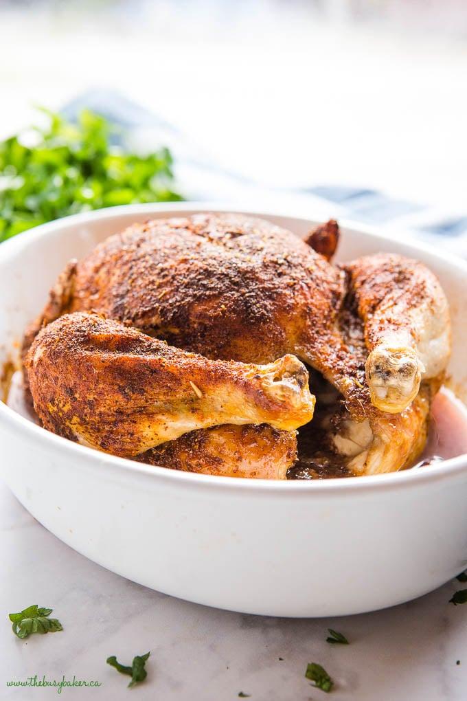whole rotisserie chicken in white baking dish
