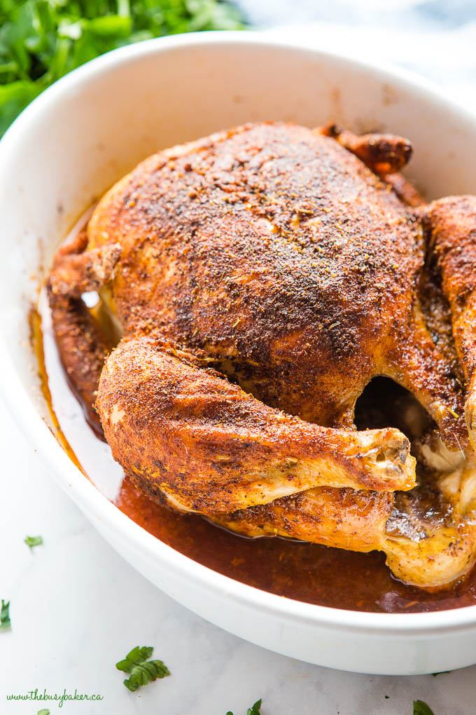 golden brown roast chicken coated in spices, in baking dish