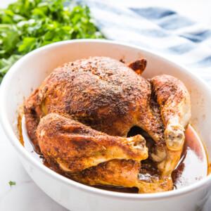homemade rotisserie chicken in white serving dish