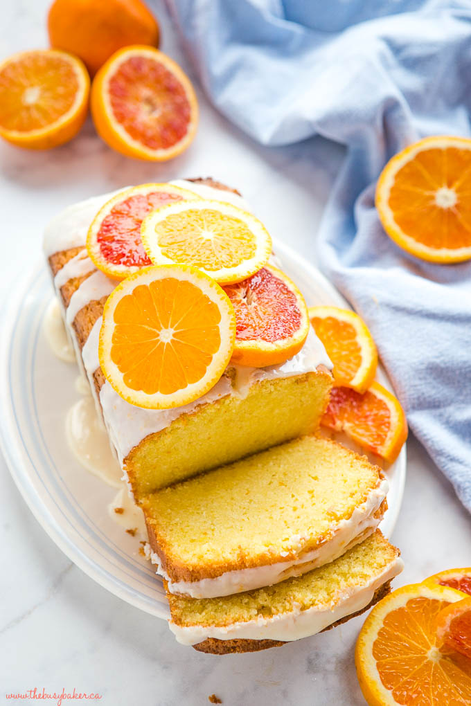 overhead photo: moist loaf cake with orange glaze and fresh orange slices on white platter