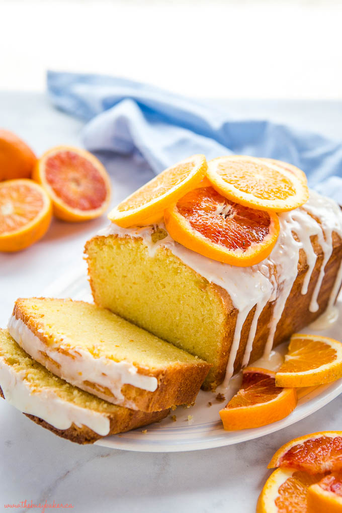 moist loaf cake topped with citrus glaze and fresh orange slices