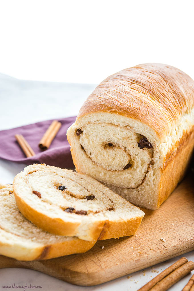 cinnamon raisin bread loaf with 2 slices cut from it on wood cutting board