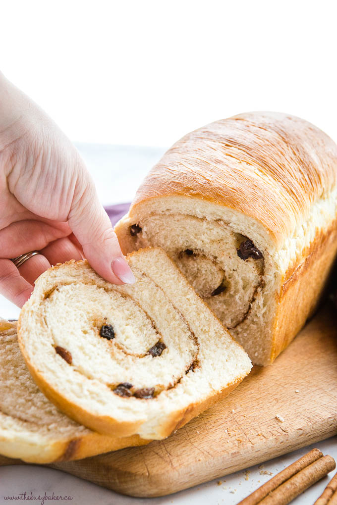 hand reaching for a slice of homemade bread with cinnamon and raisins in it