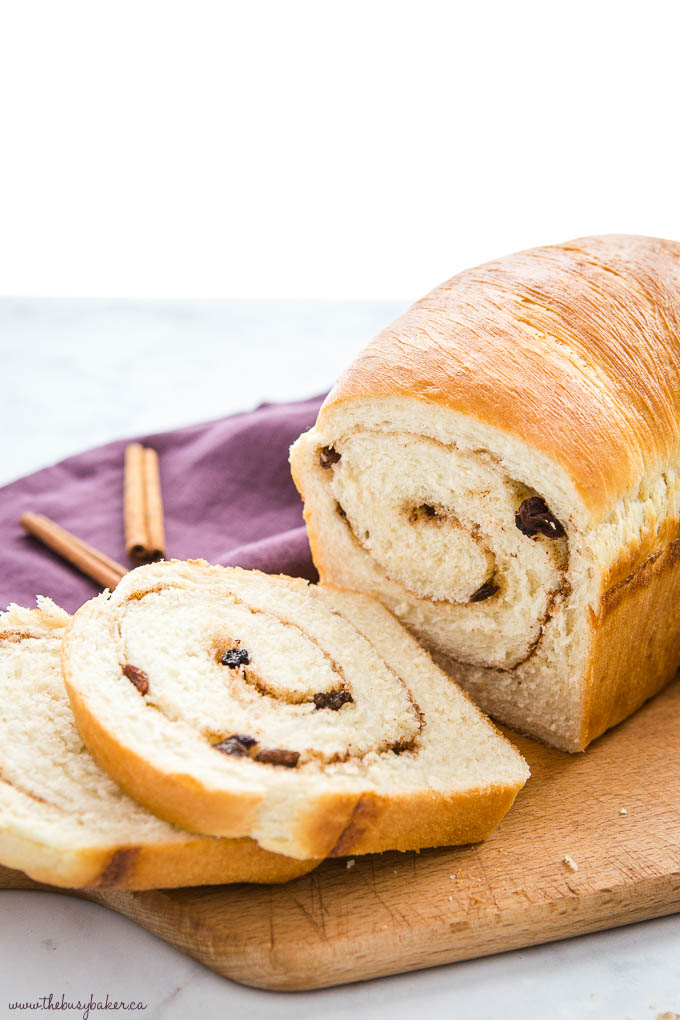 cinnamon raisin bread recipe, freshly baked and sliced, on cutting board