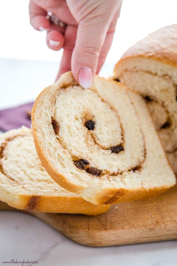 hand reaching for a slice of cinnamon raisin bread