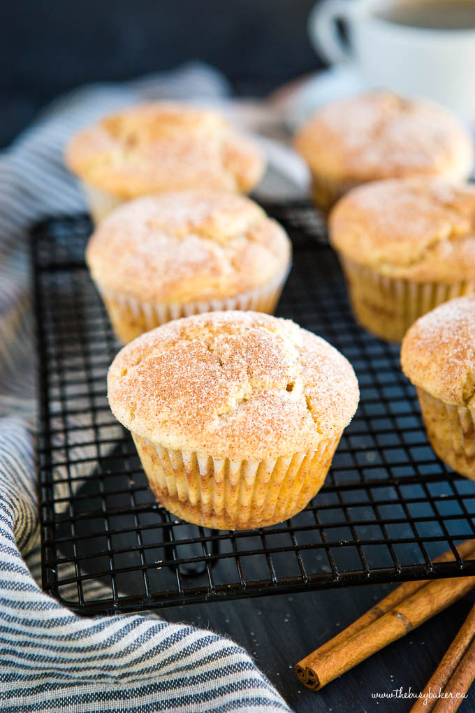 six cinnamon muffins topped with cinnamon sugar on black wire cooling rack