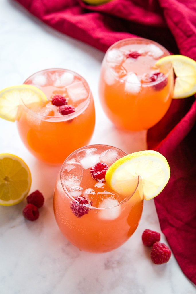 3 drinking glasses full of ice and fruit punch with lemon slices on the rim