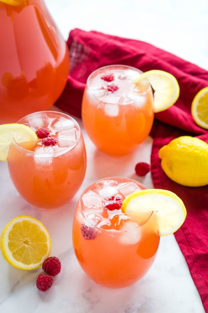 3 glasses of party punch with ice cubes and lemon slices