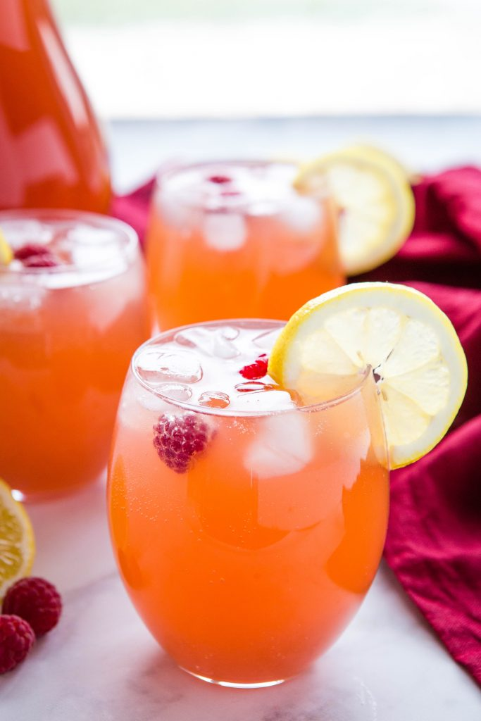 3 glasses of easy party punch with lemon slices, ice and raspberries