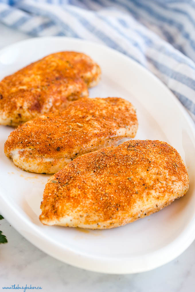 juicy baked chicken breasts on white platter