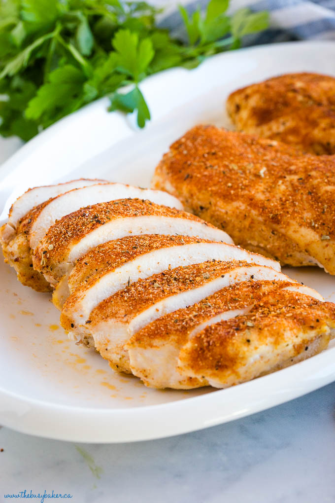 juicy slices of oven baked chicken breast on a white platter