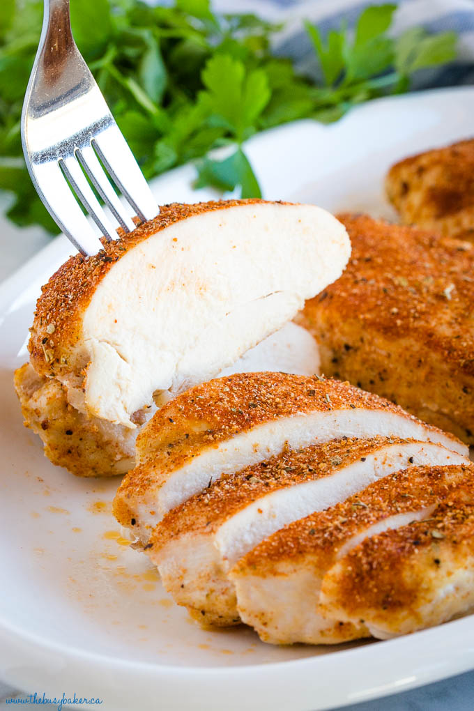 fork in slice of 5 spice oven baked chicken breast