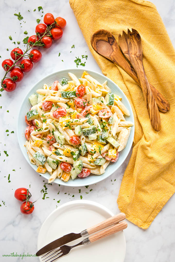 pasta salad in blue bowl with yellow kitchen towel, wood salad tongs and cherry tomatoes on the vine