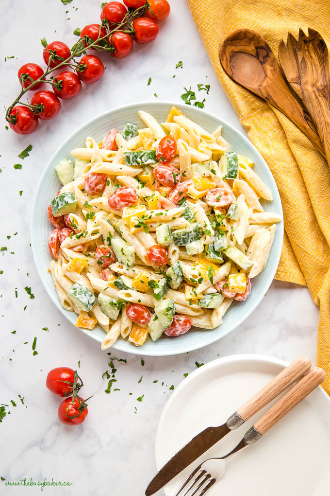 pasta salad in blue bowl with cherry tomatoes