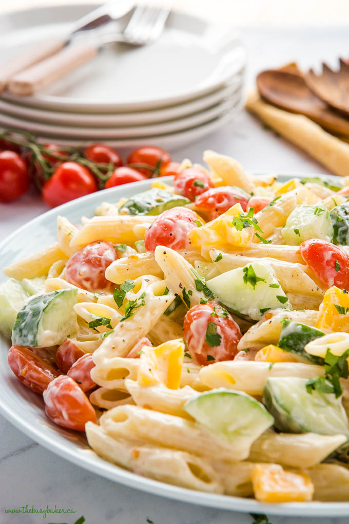 pasta salad with penne, tomatoes, cucumbers and yellow peppers in a pale blue bowl