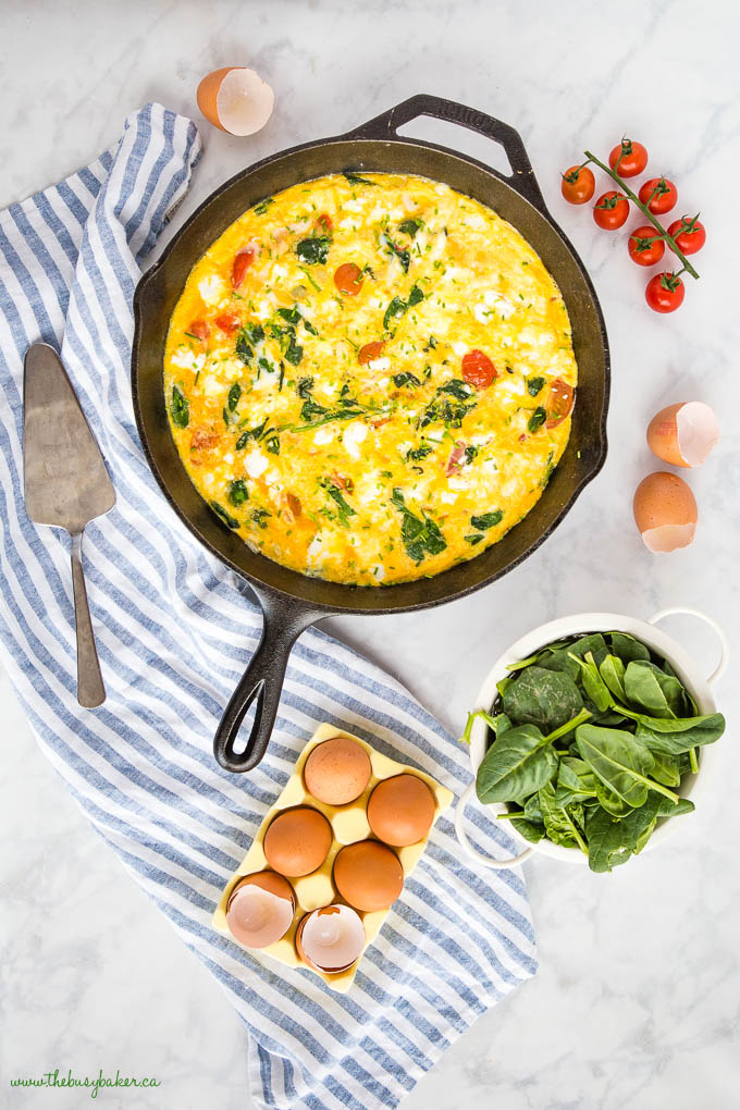 tomato and spinach frittata in cast iron skillet with eggs, cherry tomatoes and fresh spinach