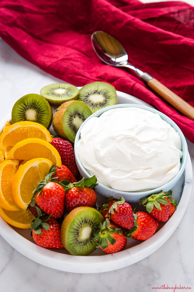 marble platter with strawberries, oranges, and kiwis, and white fruit dip in blue bowl with spoon