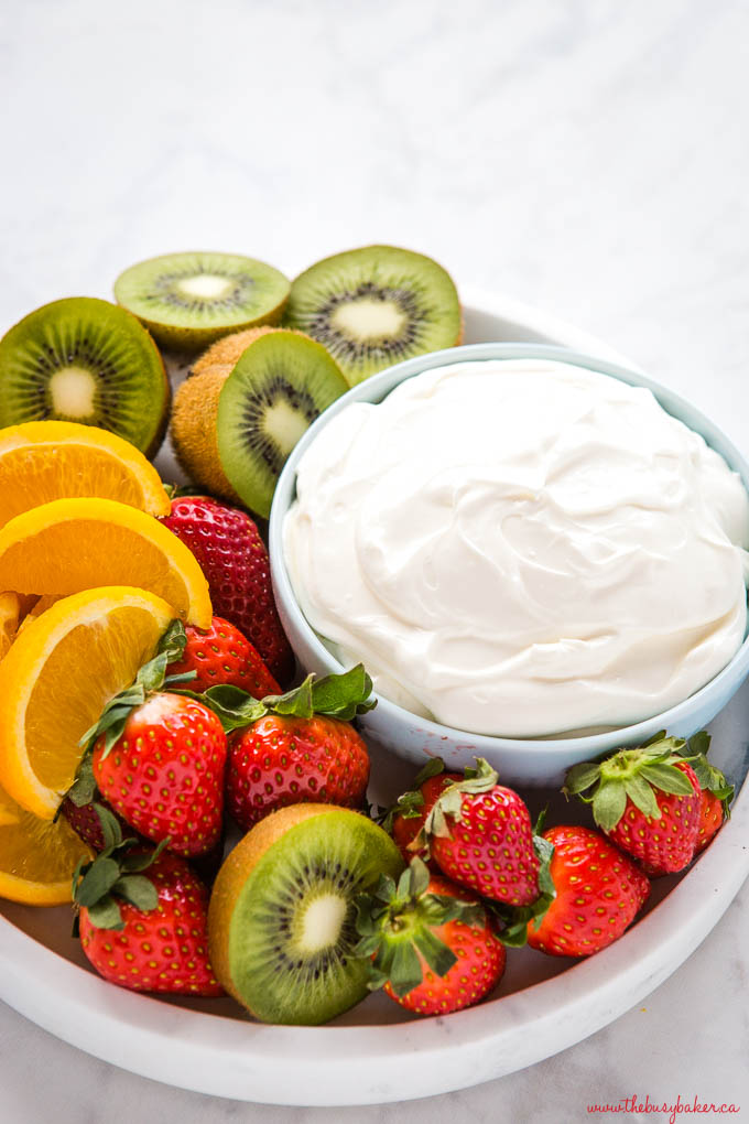 white dessert dip on blue bowl with strawberries, oranges, and kiwis