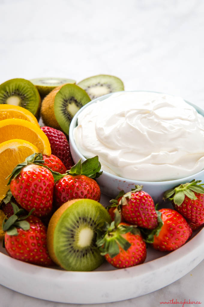 strawberries, oranges and kiwis on marble platter with blue bowl of white fruit dip