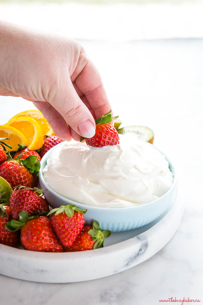 hand dipping strawberry into bowl of fruit dip on marble platter with strawberries, oranges, and kiwis