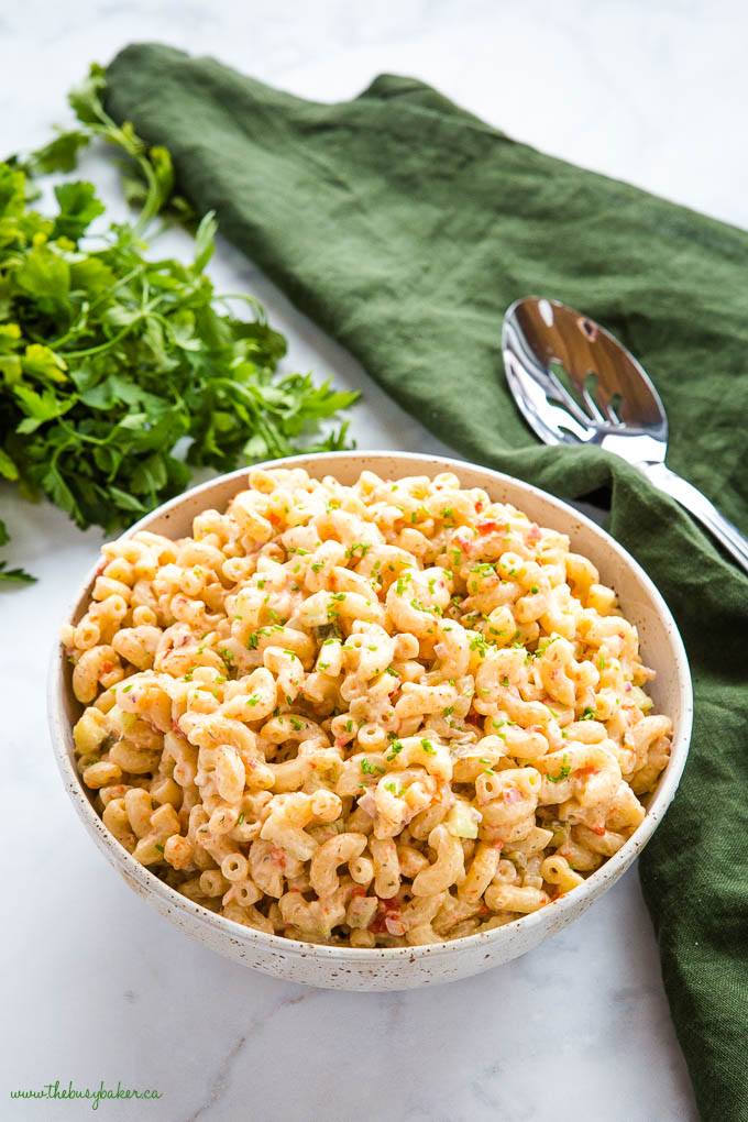 macaroni salad in pottery bowl with fresh herbs