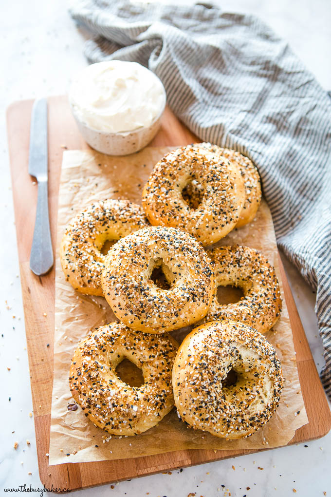 homemade everything bagels on wood cutting board with cream cheese and knife