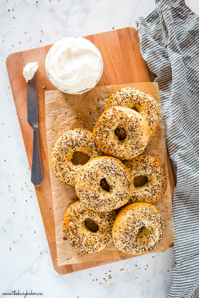 everything bagels on wooden cutting board with parchment paper and cream cheese