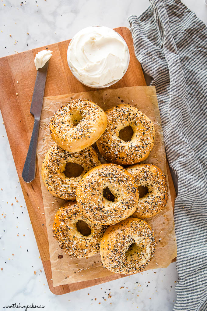 homemade everything bagels on wooden board with cream cheese on knife