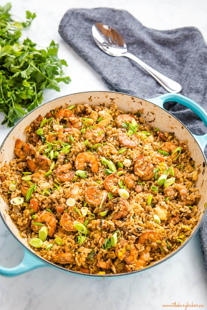 turquoise cast iron pan full of shrimp fried rice on marble counter