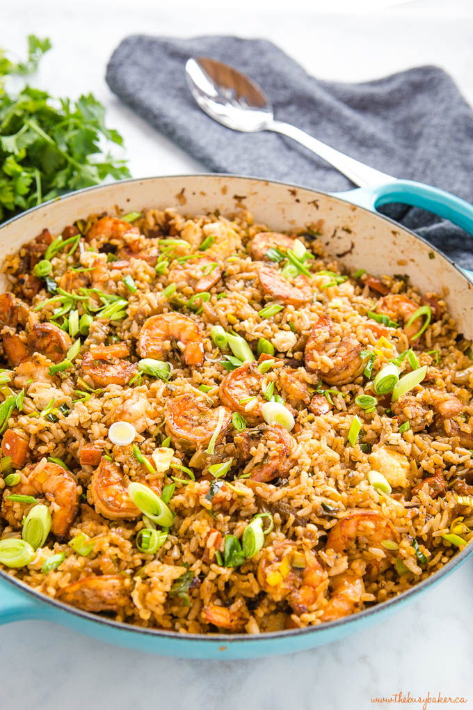 shrimp fried rice with green onions in cast iron pan with spoon