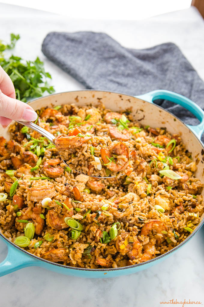 hand holding spoon of shrimp fried rice over cast iron pan
