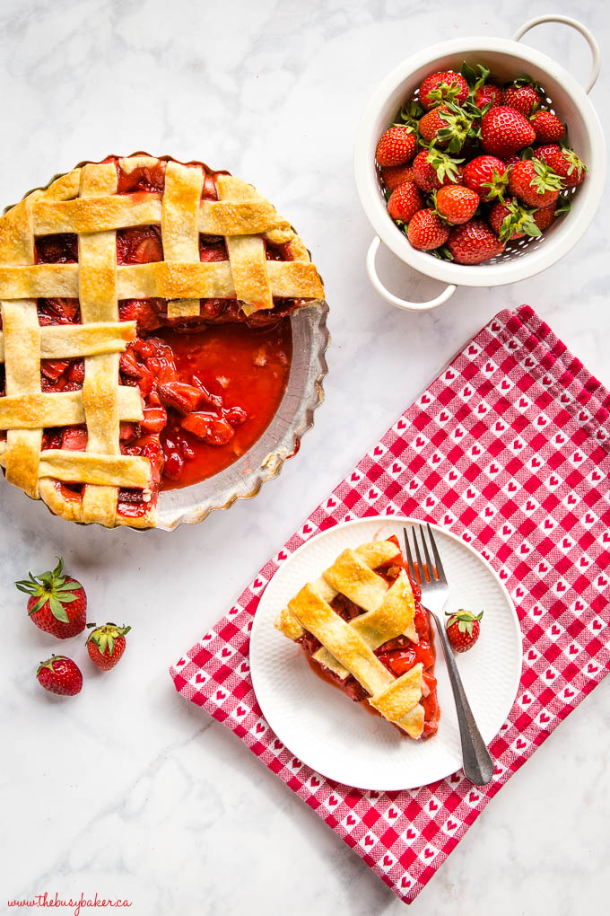 juicy strawberry pie with strawberries and slice of pie on a white plate