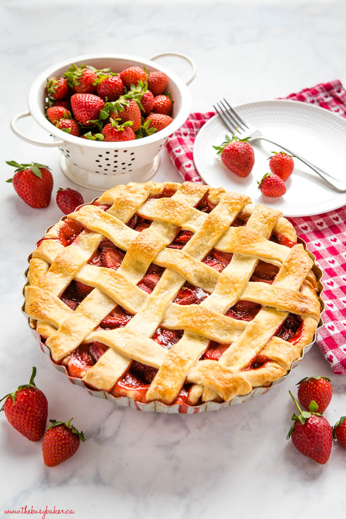 strawberry pie with golden lattice pie crust on a white marble counter with fresh strawberries