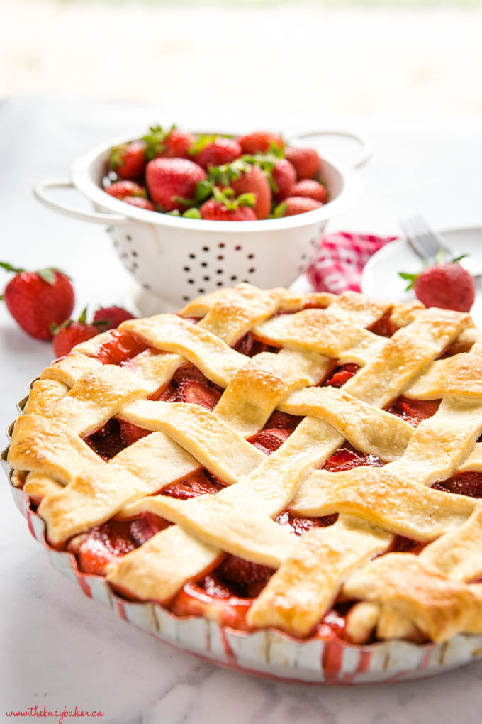 baked strawberry pie in aluminum old fashioned pie dish with fruit juice dripping down the sides