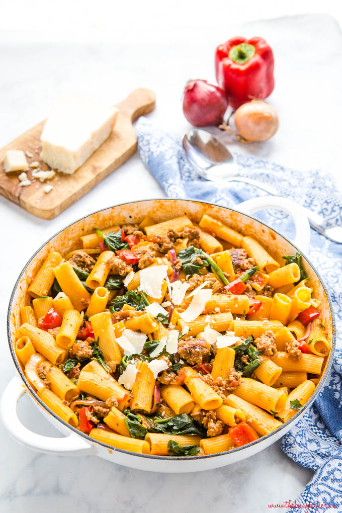 one pot Italian sausage pasta in white cast iron pan with parmesan, spinach and peppers