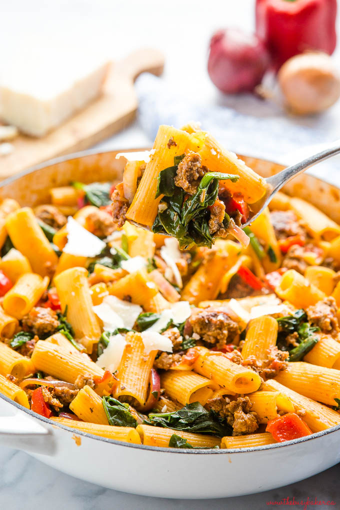 spoonful of Italian sausage pasta with spinach and peppers