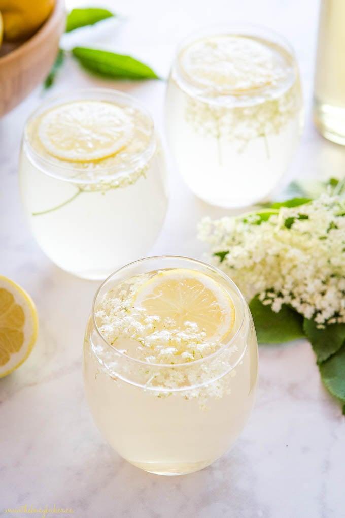 elderflower cocktails in stemless wine glasses garnished with fresh lemon slices