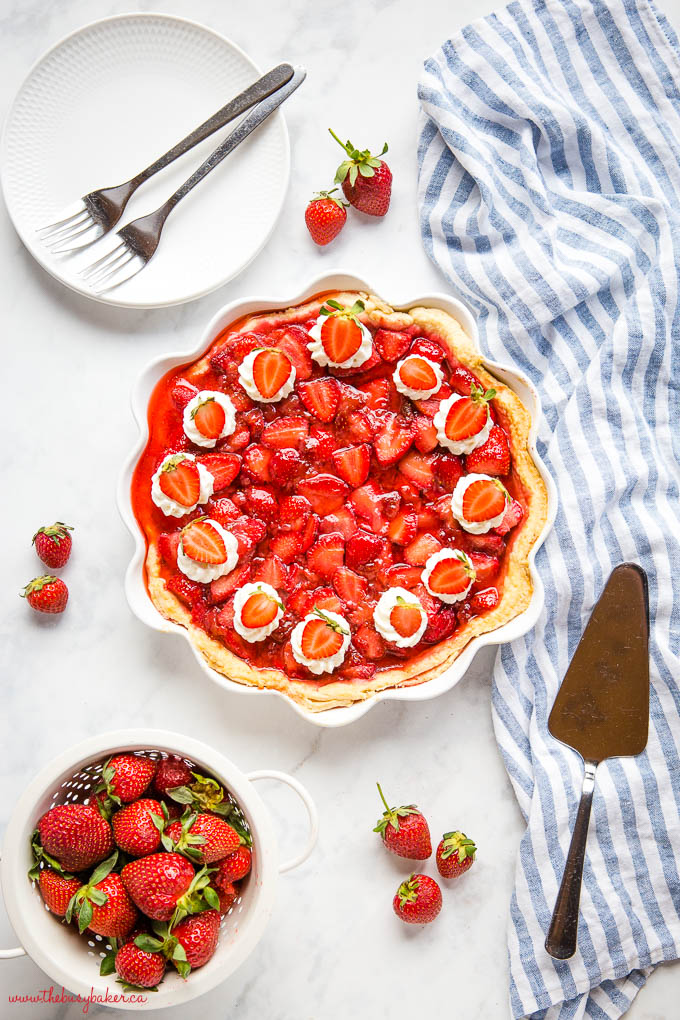 overhead image: fresh strawberry pie with whipped cream and strawberries