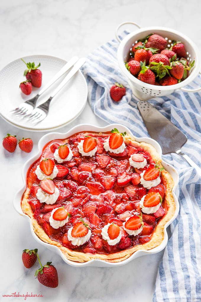 whole fresh strawberry pie with whipped cream and fresh strawberries