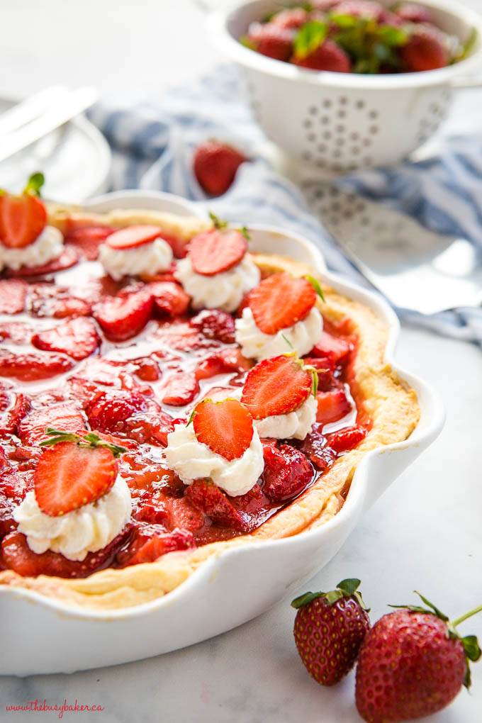 close up image of fresh strawberry pie in white pie dish