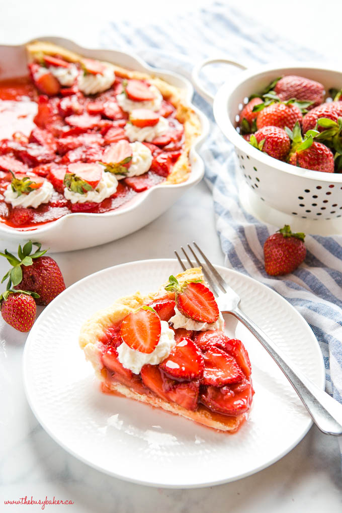 fresh strawberry pie slice on white plate with whipped cream and sliced berries